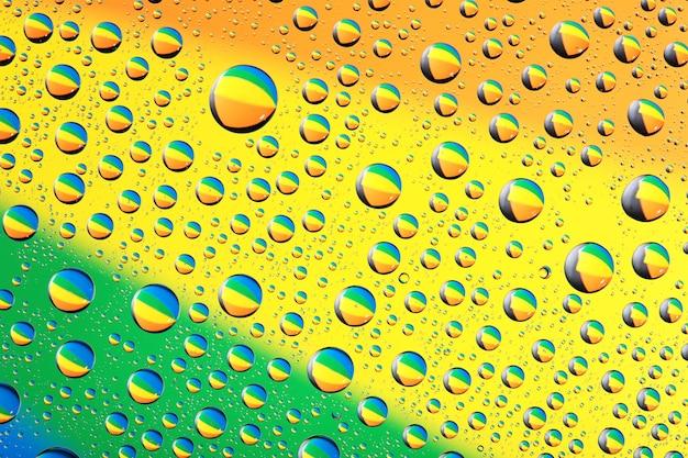 Wassertropfen-hintergrund auf grüner, gelber, oranger farbe