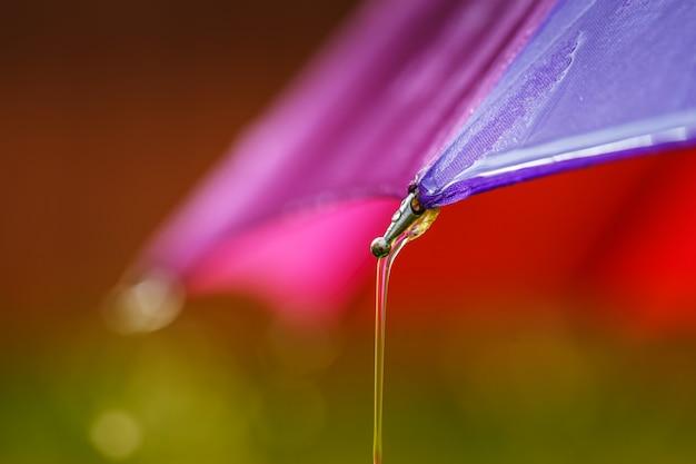 Wassertropfen laufen vom regenschirm herunter.