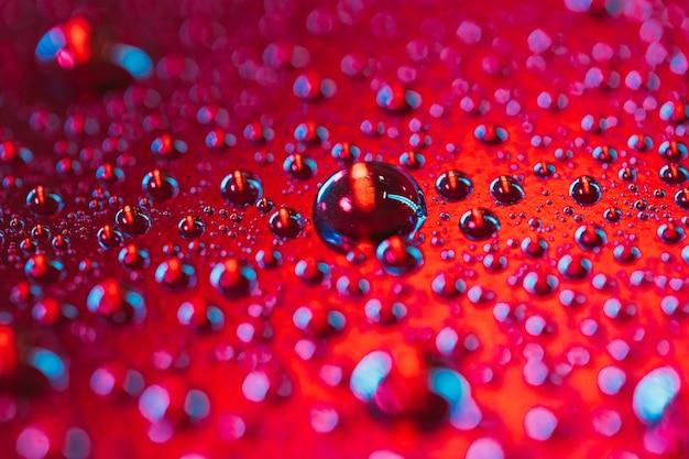 Wassertropfen sprudelt auf der oberfläche des roten hintergrundes