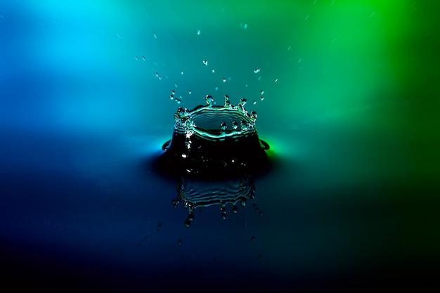 Wassertropfenspritzen auf nettem hintergrund des blauen grüns