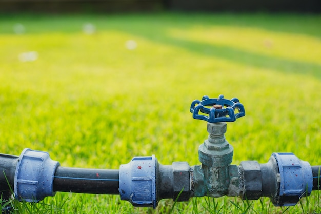 Wasserventilrohr im grünen gartengrasfeld