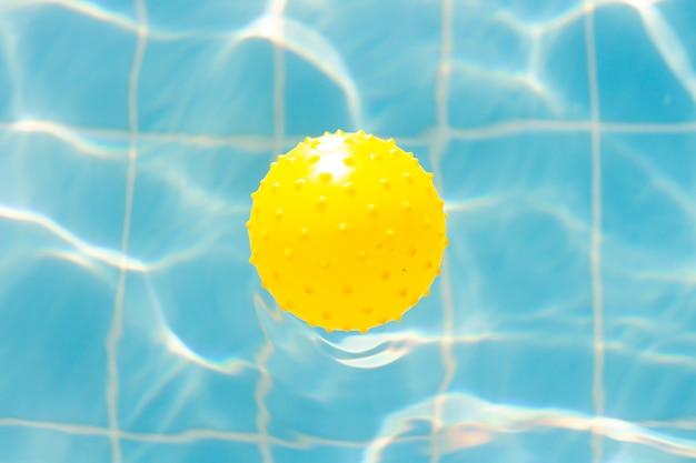 Wasservibrationen im schwimmbad mit sonnenreflexion und gelbem ball zum spielen. blaue schwimmbadoberfläche, wasser im schwimmbad. flache lage, draufsicht