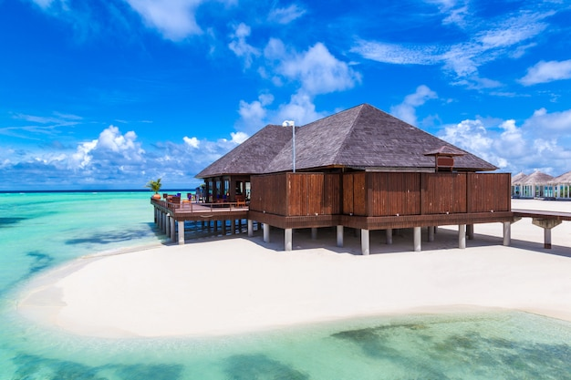 Wasservillen und holzbrücke am tropischen strand auf den malediven