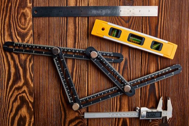 Wasserwaage, lineal und bremssattel, holztisch. professionelle instrumenten-, tischler- oder baumaschinenausrüstung, holzbearbeitungswerkzeuge