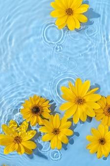 Wasserwelligkeit mit gelben blumen. trendiger hintergrund für die präsentation von kosmetikprodukten. künstlerisches konzept. platz kopieren