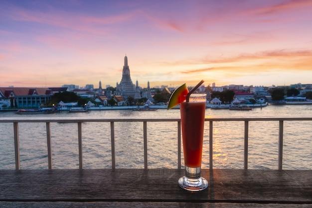 Wat arun hintergrund bei sonnenuntergang vom bar-amp-restaurant mit wassermelone in gläsern