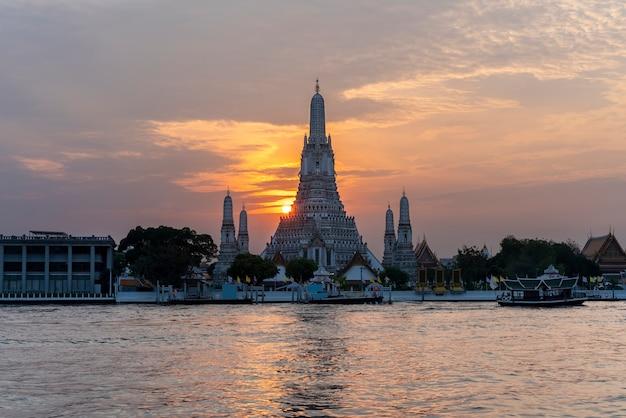 Wat arun ratchawararam ratchawaramahawihan oder wat arun, was tempel der morgenröte auf chao phraya river bei sonnenuntergang, bangkok, thailand bedeutet
