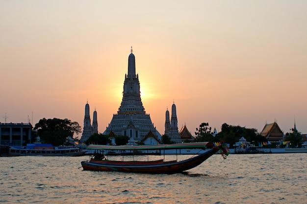 Wat arun ratchawararam ratchawaramahawihan-tempel der morgenröte mit boot des langen schwanzes bei sonnenuntergang