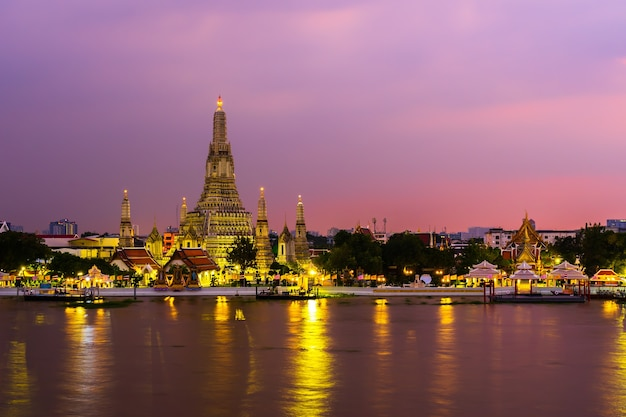 Wat arun tempel mit chao phraya fluss bei sonnenuntergang in bangkok, thailand