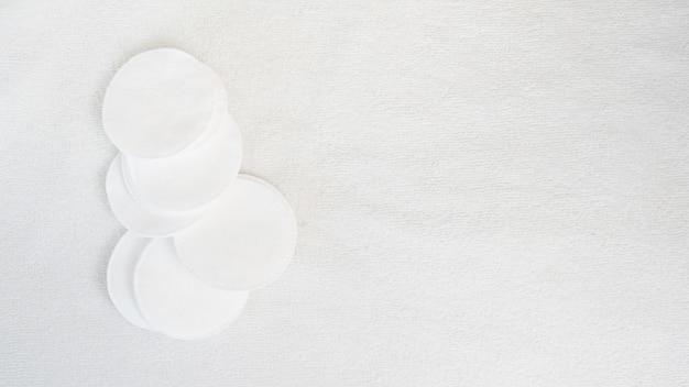 Wattepads auf weißem tuchhintergrund