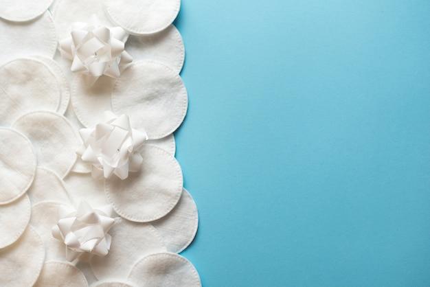 Wattepads mit weißen blumen zum entfernen von make-up auf einem blauen hintergrund