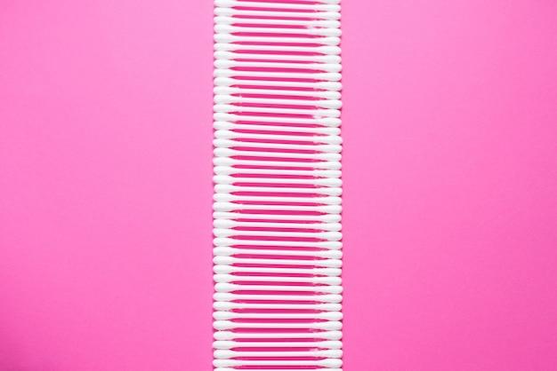 Wattestäbchen auf rosa hintergrund. kosmetisches konzept mit kopienraum.