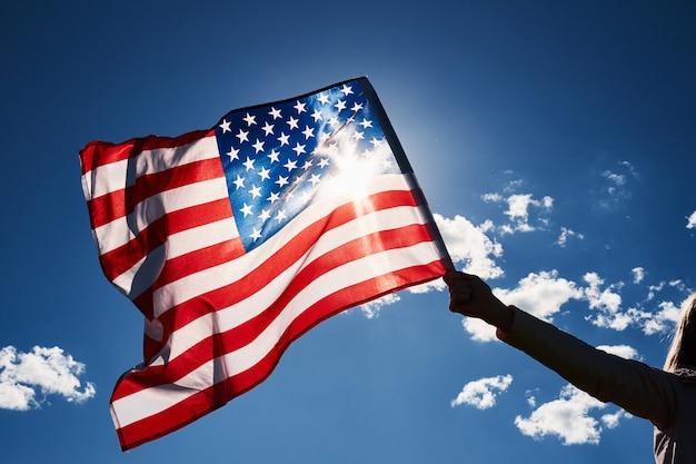 Waving usa-flagge in der hand gegen blauen himmel