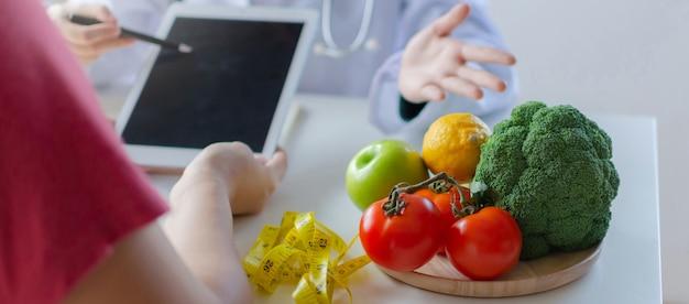 Web-banner. gemüse und früchte mit der ernährungswissenschaftlerin, die tablette verwendet und über diätplan mit patienten auf schreibtisch am bürokrankenhaus spricht