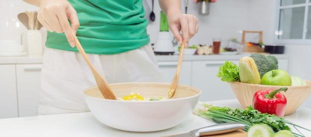 Web banner. nähren sie junge frau im grünen hemd, das zu hause den gemüsesalat in der schüssel für gutes gesundes in der modernen küche steht und zubereitet