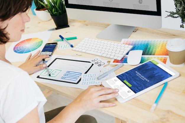 Webdesigner, der an responsivem design arbeitet. alle grafiken sind zusammengestellt.