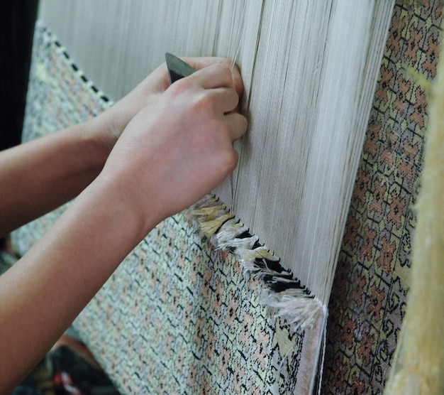 Weben und herstellung von handgefertigten teppichen, nahaufnahme. frauenhände weben einen teppich