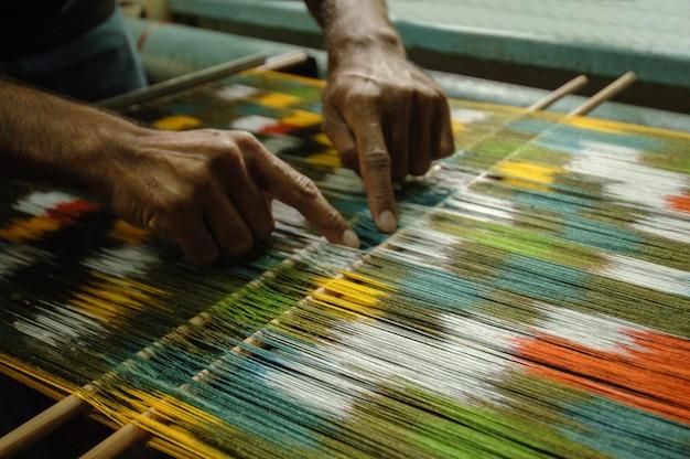 Weben und herstellung von handgefertigten teppichen, nahaufnahme. männerhände hinter einem webstuhl