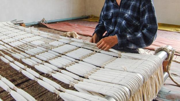 Weberei und herstellung von handgefertigten teppichen aus nächster nähe. männerhände hinter einem webstuhl