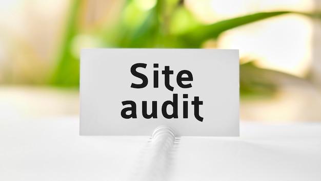 Website-audit-business-seo-konzepttext auf einem weißen notizbuch und grünen blumen