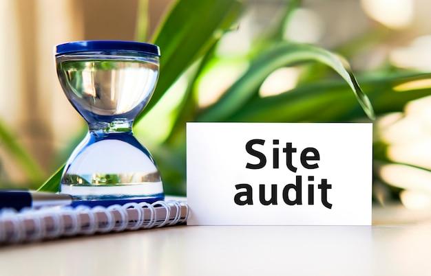 Website-audit-geschäftskonzepttext auf einem weißen notizbuch und einer sanduhr, grüne blätter von blumen