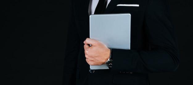 Website-banner. junger stattlicher geschäftsmann im modernen schwarzen anzug, der bewegliche tablette und stehende lage hält