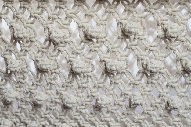 Webstruktur im makramee-stil aus weißen naturbaumwollfäden.