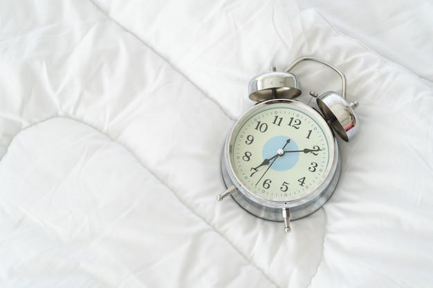 Wecker am morgen auf einem weißen bett, wachen konzept auf