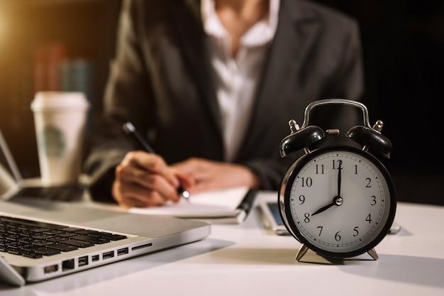 Wecker auf dem schreibtisch. geschäft, das im modernen bürogebäude oder im büro nachts unter verwendung des laptops arbeitet.
