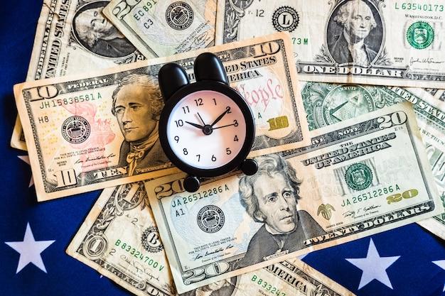 Wecker auf der amerikanischen flagge mit geld, um die beste zeit zu investieren.