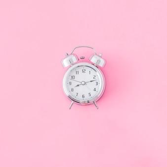 Wecker auf rosa hintergrund