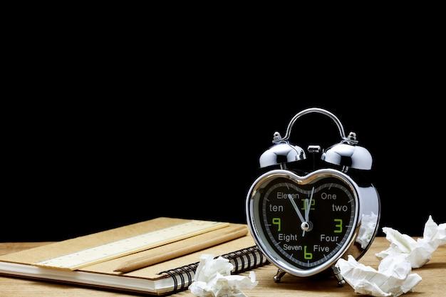 Wecker auf schwarzem hintergrund der tabelle, fünf minuten zu zwölf uhr