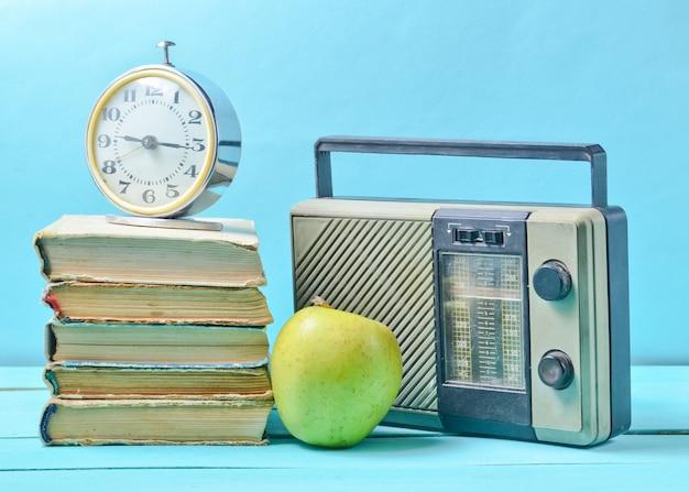 Wecker auf stapel alter bücher, radioempfänger, apfel auf blau.