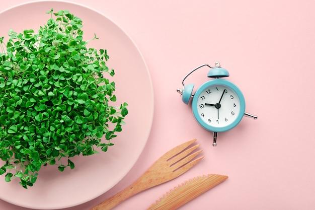 Wecker, besteck und teller mit grün auf rosa. intermittierendes fasten und diätkonzept.