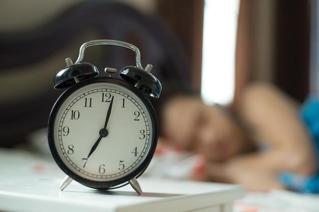 Wecker, frau faul aufzuwachen, um auf dem bett zu arbeiten.