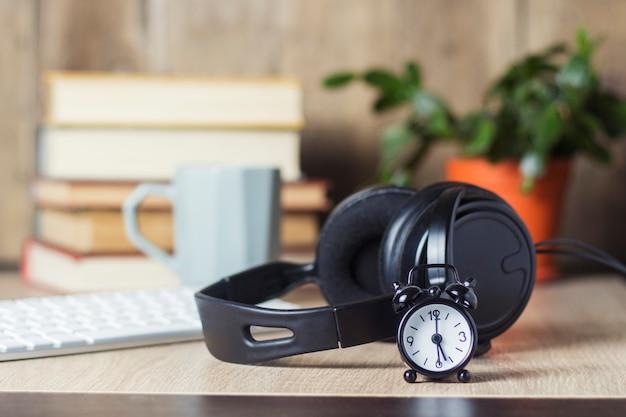 Wecker, kopfhörer und tastatur auf dem schreibtisch mit büchern. bürokonzept, arbeitstag, stundenlohn, arbeitszeitplan, arbeit in einem callcenter.