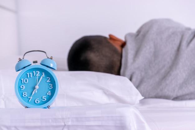 Wecker mit dem jungen, der auf bett schläft.