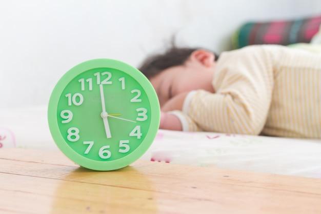 Wecker mit dem kleinen jungen, der auf bett, grüner wecker, holztisch schläft,