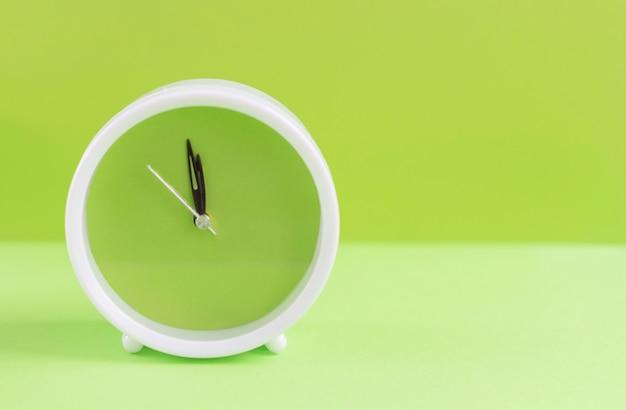 Wecker mit grünem zifferblatt auf grünem hintergrund