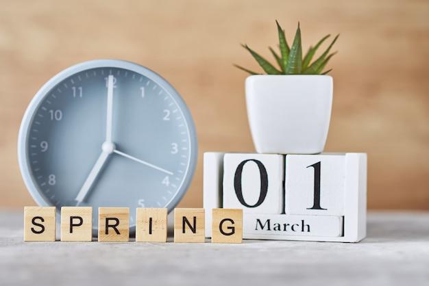 Wecker mit holzblockkalender datum 1. märz und pflanze auf tisch