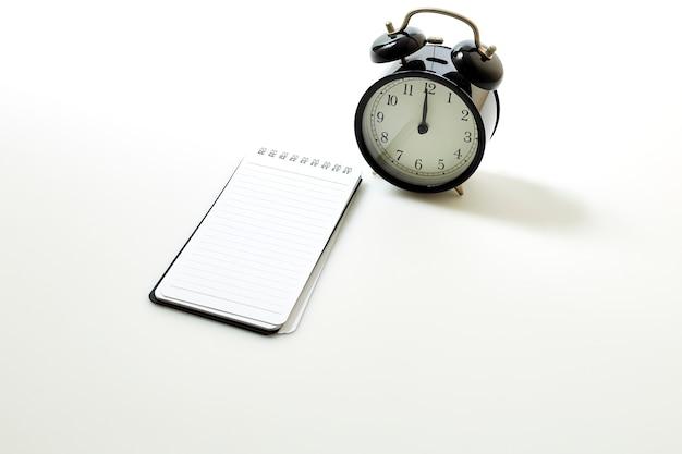 Wecker mit leerem weißem notizbuch