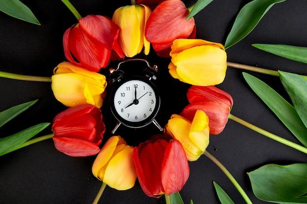Wecker mit roter und gelber tulpe herum.