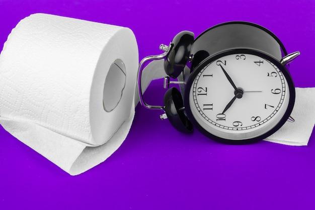 Wecker mit toilettenpapier auf einem purpur