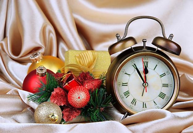 Wecker mit weihnachtsdekoration auf goldenem stoffhintergrund