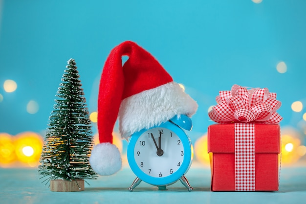 Wecker mit weihnachtsmannmütze und weihnachtsbaum und präsentkarton. zeit für weihnachten. karte mit kopienraum für text.