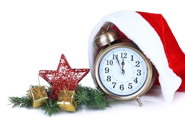 Wecker mit weihnachtsmütze und weihnachtsschmuck isoliert auf weiß