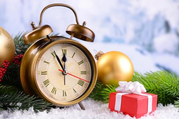 Wecker mit weihnachtsschmuck auf hellem hintergrund