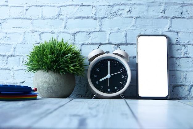 Wecker, notizblock und smartphone mit leerem bildschirm auf dem tisch.