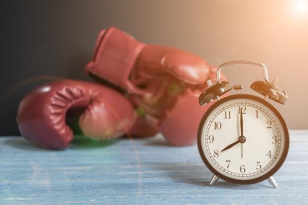 Wecker und boxhandschuhe auf holztisch