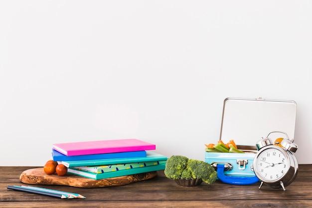 Wecker und lunchbox in der nähe von schreibwaren